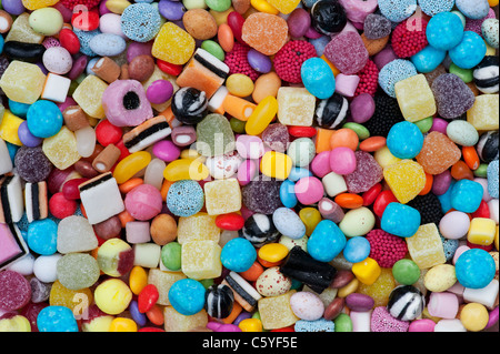 Colourful childrens sweets pattern. Liquorice allsorts, Smarties, pineapple cubes, humbugs, bonbons, dolly mixtures - Stock Photo