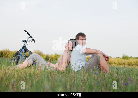 Russia, Voronezh, couple sitting in meadow - Stock Photo