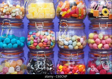 Colourful childrens sweets in kilner jars. Liquorice allsorts, Smarties, pineapple cubes, humbugs, bonbons, dolly - Stock Photo