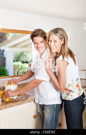 Couple using a juicer in kitchen - Stock Photo