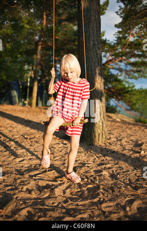 Girl playing on tree swing in forest - Stockfoto