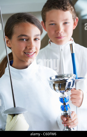 Smiling girl holding fencing trophy - Stockfoto