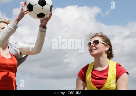 Girls playing soccer together - Stock Photo