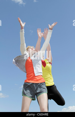 Girls jumping for joy against blue sky - Stock Photo