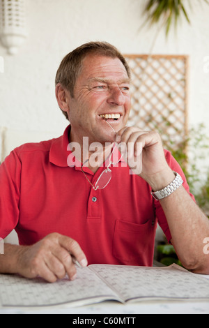 Older man completing crossword puzzle - Stock Photo