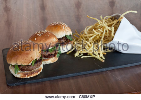 Burgers and french fries on plate - Stock Photo