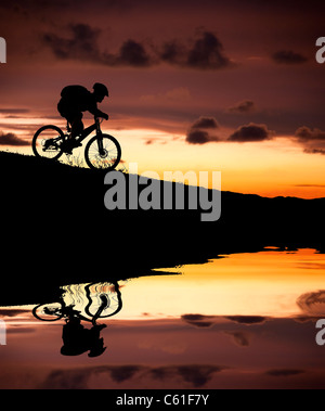 silhouette of mountain biker with Reflection and sunset - Stock Photo