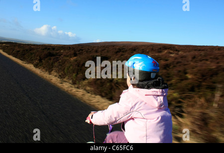 Young child cycling on a single track road - Stock Photo