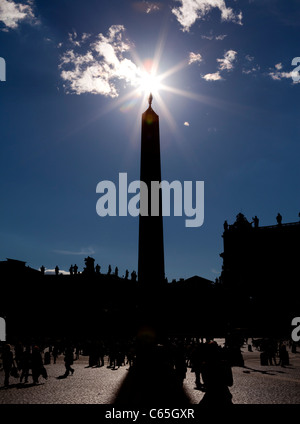 Sun star silhouettes the obelisk in St Peters Square, Vatican City, Rome, Italy. - Stock Photo
