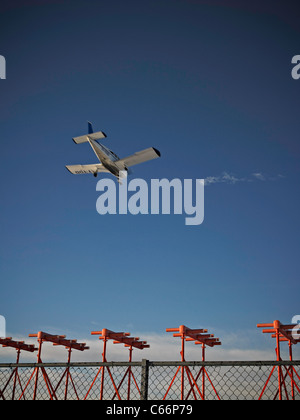 Airplane flying over fence - Stock Photo
