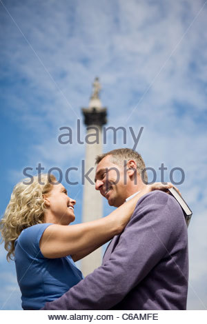 A middle-aged couple embracing in front of Nelson's column - Stock Photo