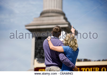 A middle-aged couple standing in front of Nelson's column, woman pointing - Stock Photo