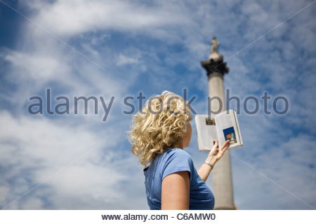 A middle-aged woman in front of Nelson's column, looking at a guidebook - Stock Photo