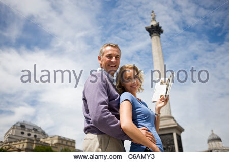 A middle-aged couple in front of Nelson's column, holding a guidebook - Stock Photo