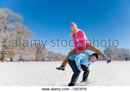 Woman jumping over man's back in sunny, snowy field - Stockfoto