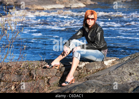 Young redheaded woman is sitting on the rock near by river on sunshine - Stockfoto