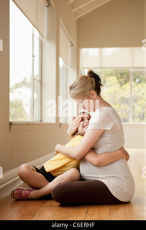 USA, California, Beverley Hills, Daughter embracing pregnant mother - Stock Photo