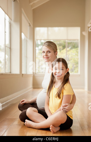 USA, California, Beverley Hills, pregnant mother and daughter practicing yoga - Stock Photo