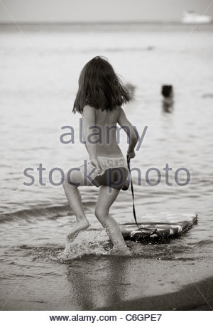 Boy child playing in sea water at the beach on a summer evening at dusk - Stock Photo