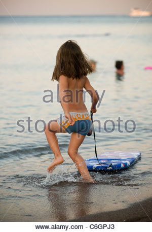 Boy child playing in sea water at the beach on a summer evening at dusk - children water toys splashing seaside - Stock Photo