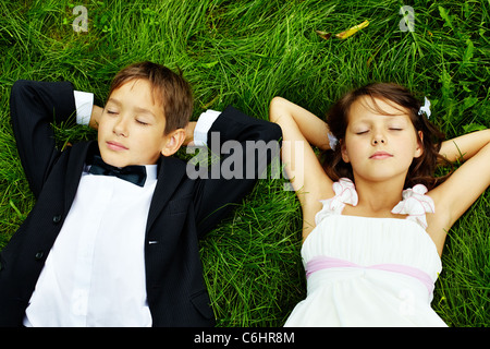 Portrait of calm children bride and groom lying on green grass - Stock Photo