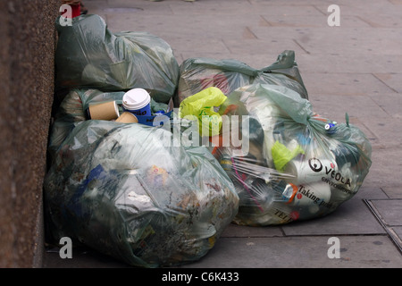 Plastic bags full of rubbish left on a pavement - Stock Photo