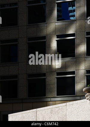 detail of empty office building plaza with stone ledge in bright sunshine seen dramatically against dark building - Stock Photo