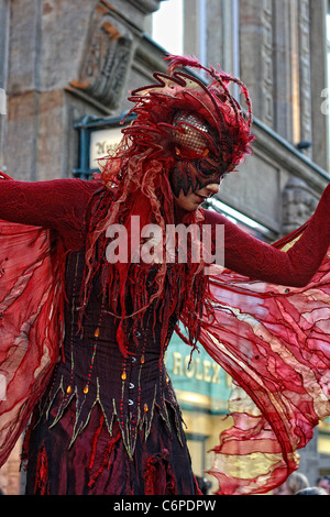 A woman dressed like a mythical creature is walking on stalks in the center of Leipzig, Germany. - Stock Photo