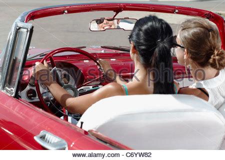Women driving vintage convertible - Stock Photo