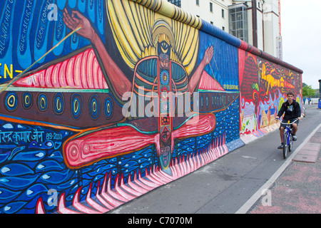 part remaining piece painted berlin wall germany man boy bicycle cycle cycling past color colorful colourful - Stockfoto