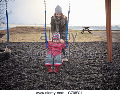Mother and daughter playing on swings - Stock Photo