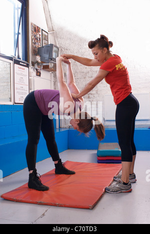 Woman stretching with trainer in gym - Stock Photo