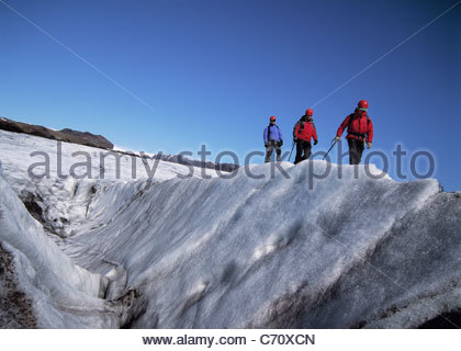 Hikers walking on glacier - Stock Photo