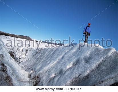 Hiker walking on glacier - Stockfoto