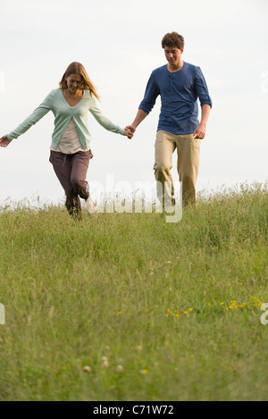 Young couple walking on meadow holding hands - Stock Photo