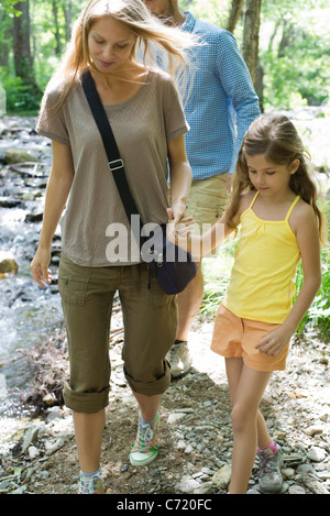 Mother and daughter walking hand in hand outdoors - Stock Photo