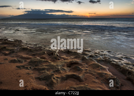 A beautiful sunset over a Maui beach with the waves lapping over the coral on the beach - Stock Photo