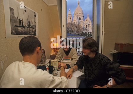 Students in an attic flat, apartment with view of the Sacre Coeur, Paris, France - Stock Photo