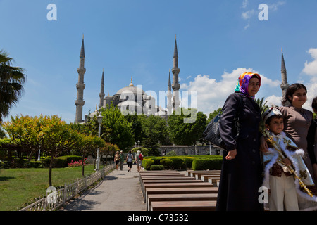 Young Turkish boy in their ceremonial circumcision outfit, posing with his family, outside the The Blue Mosque, - Stock Photo
