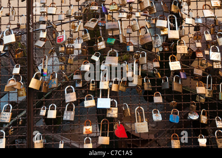 Pad locks attached to a metal grid display messages of everlasting love and commitment, Borghetto Italy - Stock Photo