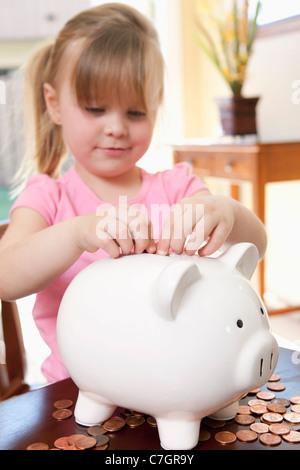 A girl putting coins into a piggy bank - Stock Photo