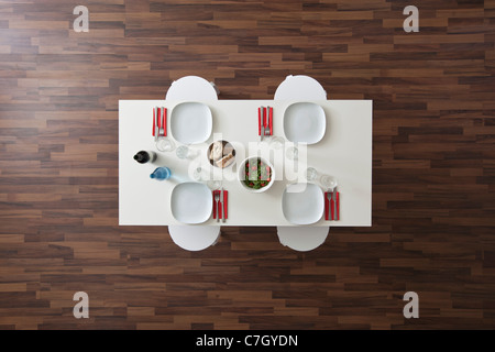 A table with place settings, wine, water, salad and bread, no people, overhead view - Stock Photo