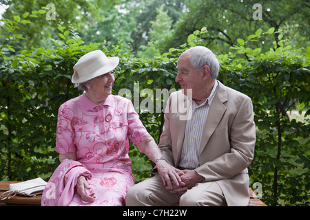 Romantic senior couple on bench in the park - Stock Photo