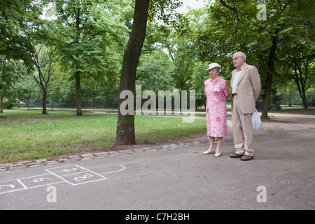 Senior couple contemplate hopscotch in the park - Stock Photo
