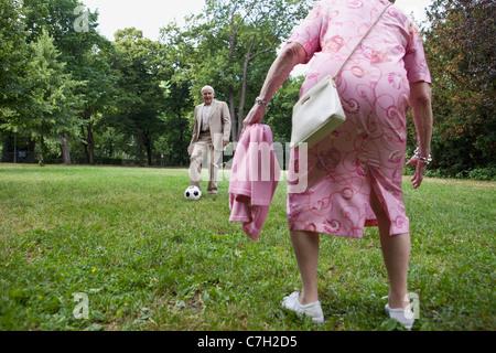 Senior couple play soccer in the park - Stock Photo