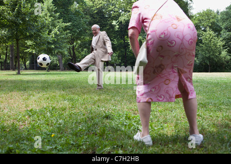 Senior couple play football in the park - Stock Photo