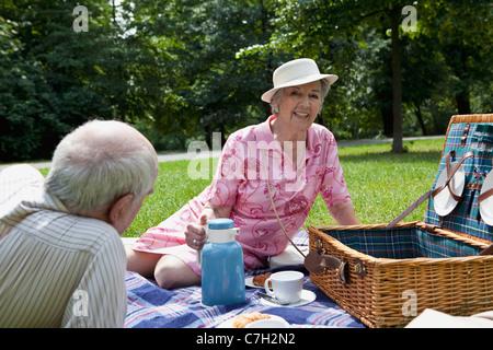 Senior couple having relaxing picnic in park - Stock Photo