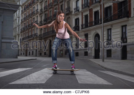 Woman riding skateboard on city street - Stock Photo