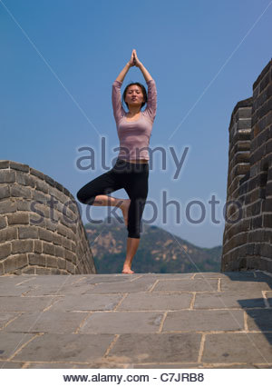 Woman balancing on Great Wall of China - Stock Photo
