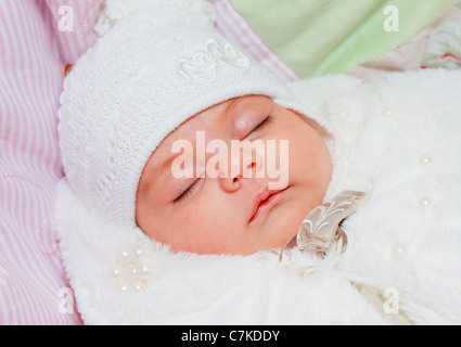 Portrait of a sleeping newborn baby, girl, the child is lying on her back. - Stockfoto